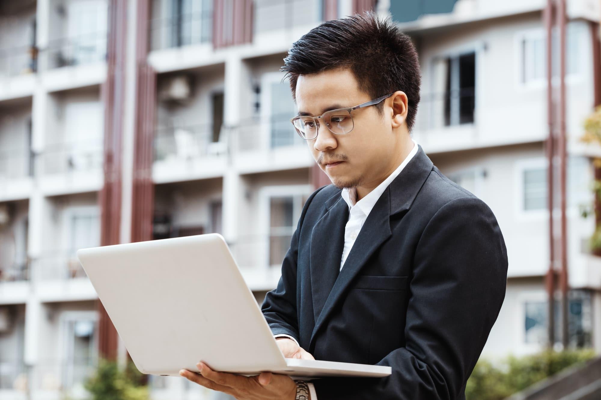 概念业务-英俊的亚洲业务人致力于与笔记本电脑的房地产投资